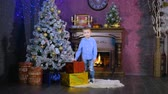 праздничный : A boy places colorful wrapped presents under a Christmas tree. Стоковые видеозаписи