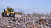 hurda : Two landfill compactors move across a landfill side.