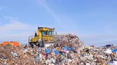 aterro : A landfill compactor bulldozer levels down a pile of trash. Water, air contamination concept. Stock Footage