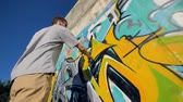 repaint : A low view on a man restoring a graffiti painting.