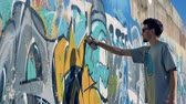 urban renewal : An artist adds some paint to a finished graffiti.