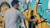 urban renewal : A male artist repaints an old graffiti wall.