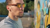 grafiti : A graffitists face in reflective glasses at work.