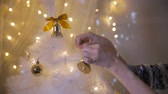 csecsebecse : Female hands decorate a tree under bright lights.