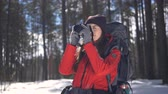 фотограф : Smiling happy young woman hiking in winter forest taking pictures using photocamera. Стоковые видеозаписи
