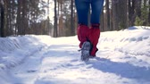 tempestade de neve : Female hiker legs walking on a snow road.