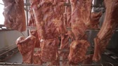 свинина : Grilled pork ribs hanging on a storage rack at food factory.