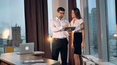 explicando : A businesswoman joins a businessman for discussion in modern office. Stock Footage