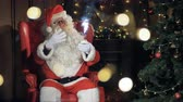 poczekalnia : Pleasing Santa Clause sits into his chair in front of a Christmas tree.