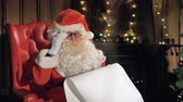 correspondência : Close-up santa Claus reading letters near Christmas fireplace. 4K. Stock Footage