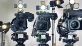 spotlight : Several video cameras with working lights.