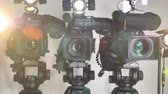 microphone : A zooming out shot on three brightly lit video cameras.