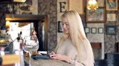 paypass : Attractive female customer uses smartphone to make a wireless payment using NFC technology.
