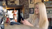 paypass : Attractive female at cafe making online payment using smartphone. 4K. Stock Footage