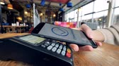 paypass : Smartphone payment. Female hand pay using nfc system and contactless card.