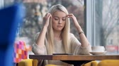 coffee table : A blonde girl gets sad after looking at her smartphone. Stock Footage