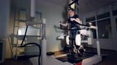 sling : A young man trains inside a large medical exoskeleton system. Stock Footage
