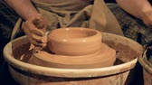earthenware : A potter shapes a basic shallow bowl on a wheel.