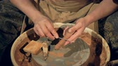 скребок : A potter uses a cleaning tool on a greenware handle.