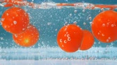 immerse : Red tomatoes splash in blue fresh water. High speed camera shot. Stock Footage