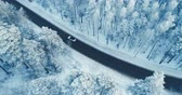 kluzký : Aerial view of a car driving on a snowy forest road. 4K.