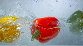 paprika : Three sweet peppers dive into clear water.