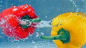 çarpmak : A red and a yellow peppers fall down into water.