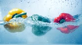 sweet pepper : A closeup on three peppers falling inside water. Stock Footage