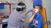 pediatrician : A doctor checks the boys throat under bright light.