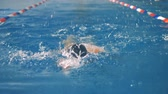 пловец : A woman swims backwards in a slow motion.