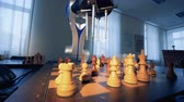 futuro : Artificial intelligence concept. Innovative modern robotic arm playing chess with a man. 4K.