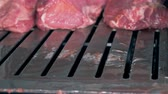 processado : Slabs of meat are being moved by cutting edges and a person is putting more meat onto the belt