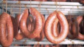 салями : Close up of sausages tied up to a metal crossbar in a factory unit Стоковые видеозаписи