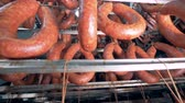 processado : Close bottom-up footage of smoked sausages tied and hanging from a metal crossbar Stock Footage
