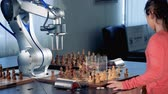 buluş : Little girl and robotic arm are capturing chess pieces of each other while playing