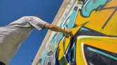 grafiti : Graffiti artist is painting a yellow letter on the wall, view from below.