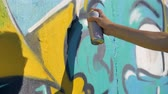 esquerda : Artists right hand is painting a yellow letter on the wall, view from the left, close up.