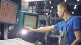 option : Worker using touchscreen operating industrial machine.