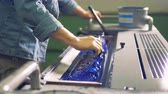 zbarvení : A man is leveling blue paint in a tray of a printing machine