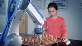 andróide : Young girl playing chess with a modern automated chess robot. Child genius concept. 4K.