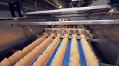 вафля : Wafer cones are being placed into each other in several rows by an industrial mechanism