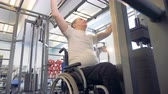 overcome : Disabled man makes exercises in a gym at training apparatus. Stock Footage