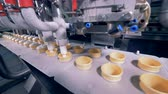 выборе : Ice-cream equipment filling wafer cones with ice-cream.