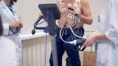 arrhythmia : Doctors are controlling a training session of a patient who is riding a stationary bicycle