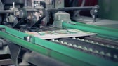 apart : Colourful printed newspapers are getting their edges cut off by a factory mechanism