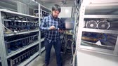 miner : Male programmer is standing in the middle of a mining farm unit with a keyboard and working