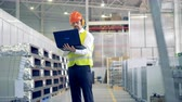 work hard : Male worker types on his laptop, standing at a warehouse, industrial plant.