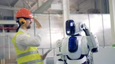 привет : Human factory worker and an android give each other a hi-five at a factory facility.