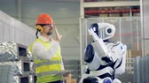 droid : A worker shows a cyborg some gestures to copy, then they give each other a hi-five. 4K.