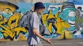 tossing up : Young man is walking along the street with graffiti painting on the background and a spray in his hands
